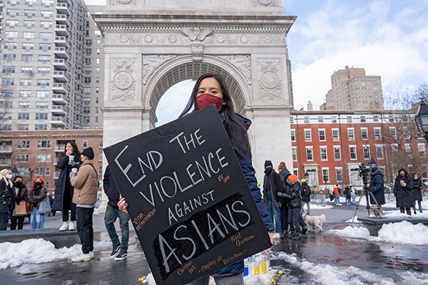 Protestor holds a sign at the End the Violence Towards Asians rally.