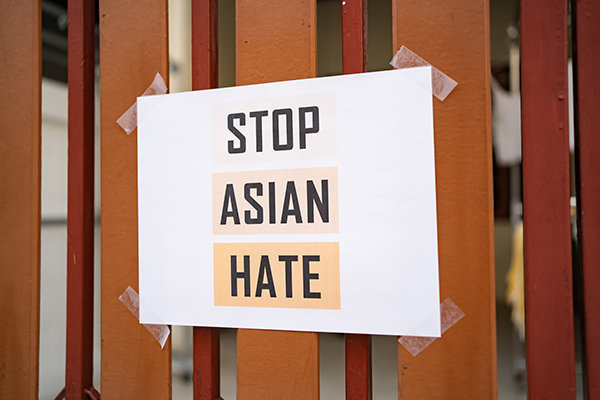 Stop Asian Hate sign taped to a fence.