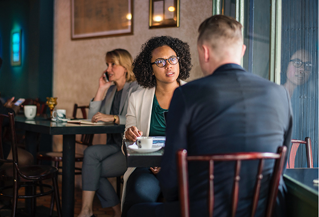 A man and a woman have a conversation while sitting at a table.