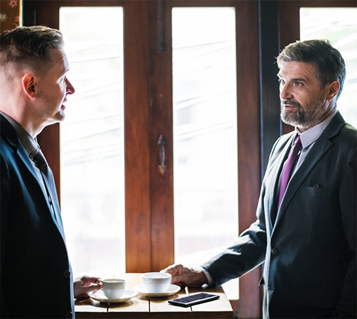 Two men, in business attire, having a conversation over coffee.