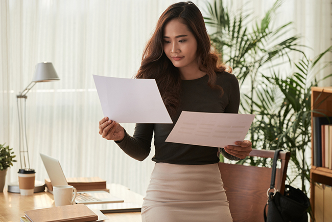 A young Asian woman in her office comparing notes.