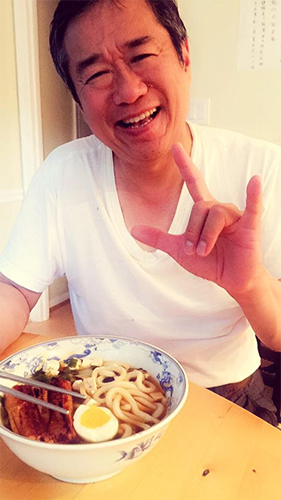 Judie's father, Frank, enjoying a bowl of udon noodles and signs I love you in American Sign Language.