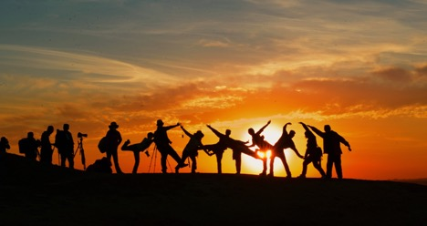A group of people posing in different manners against the setting sun.