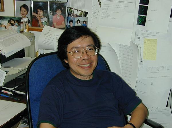 Dr. Kuan-Teh Jeang sitting at his desk.
