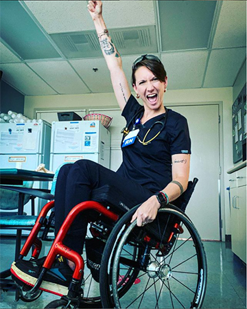 Ryann Mason in black scrubs sits in a wheelchair and pumps fist with an excited expression on her face.