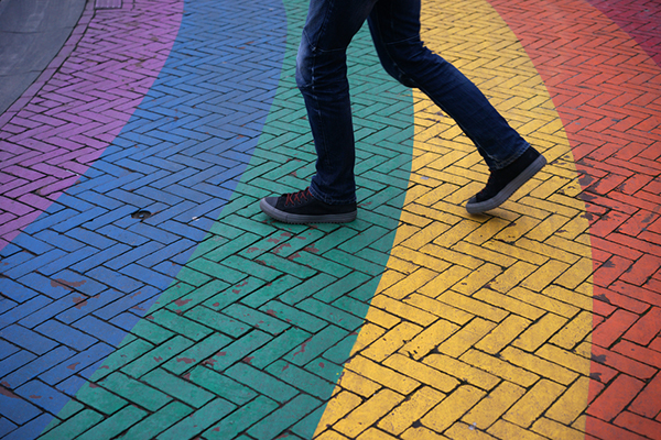 Person walking on street painted in rainbow colors.
