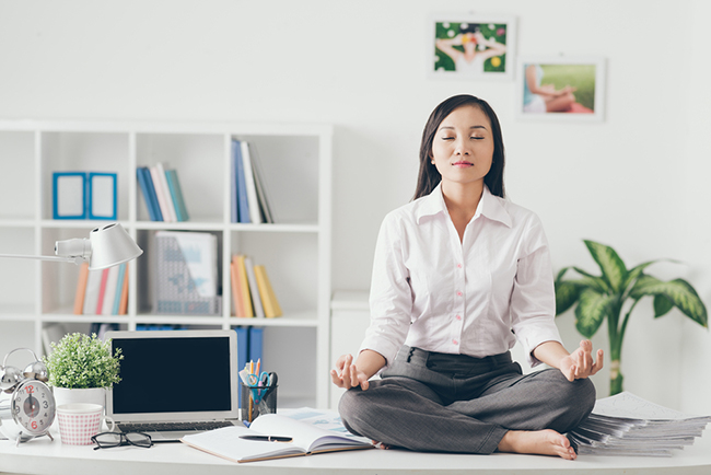 A woman sitting on her desk meditating.