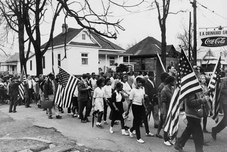 Participants, some carrying American flags, marching in the civil rights march from Selma to Montgomery, Alabama.