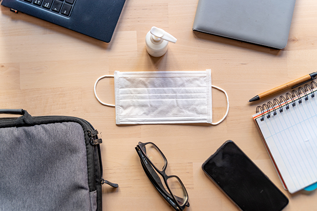 Multiple items on a desk, including glasses, phone, notepad, hand sanitizer, and mask.