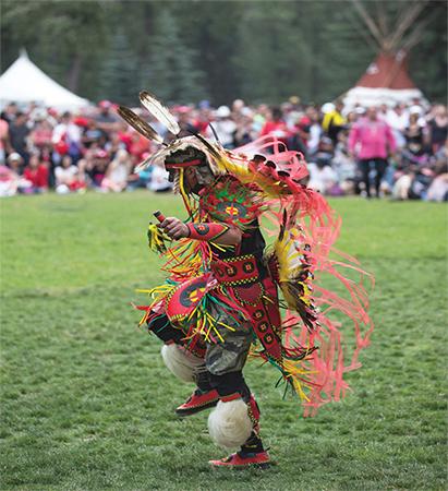 Native American man wearing full regalia dancing at a powwow.