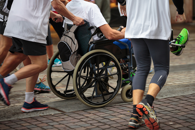 A group of people jogging. One of the runners is pushing a man in a wheelchair.