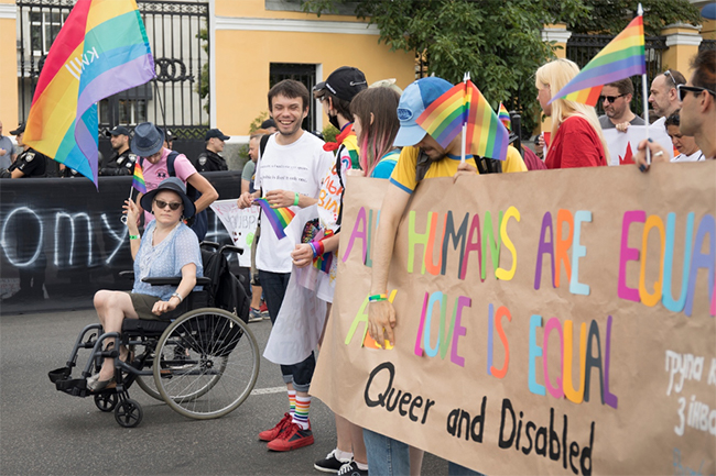 Group of people at PRIDE parade holding up banner that says: All Humans Are Equal; All Love is Equal: Queer and Disabled
