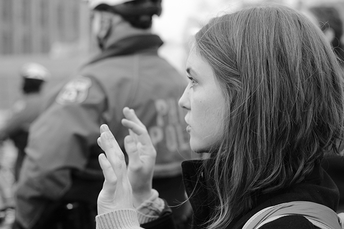 A young white woman protesting with her hands up.