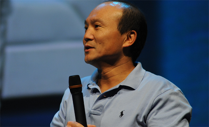 Jake Liang holding a microphone speaking to an audience.