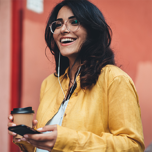 A young woman smiling while holding her coffee and phone.