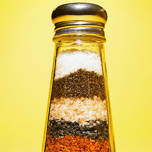 A salt shaker filled with layers of different spices.