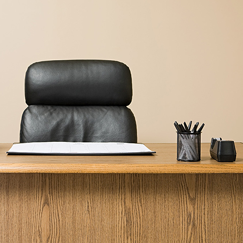 An unoccupied desk with a black executive chair and a stack of paper on the left