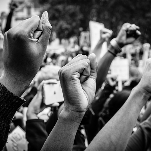 Black and white photo of fists raised in protest