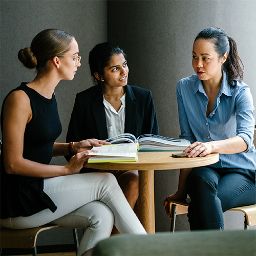 Three women sitting at a table having a conversation
