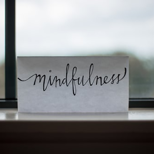Paper near window with print that reads mindfulness