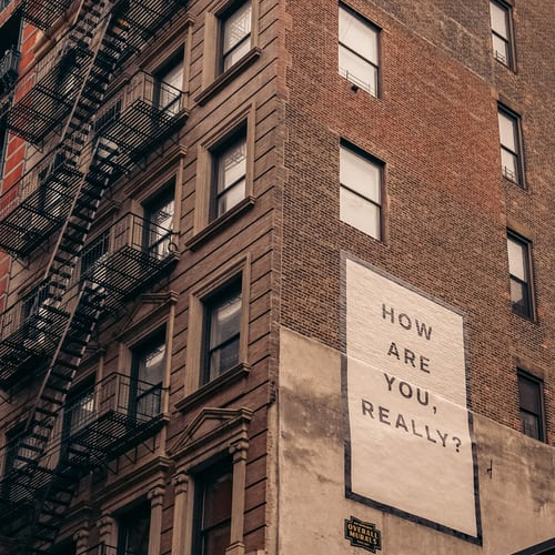 A billboard on the side of building that reads How are you really?