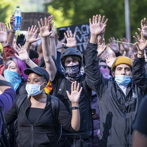 Group of masked protestors wearing black with their hands up