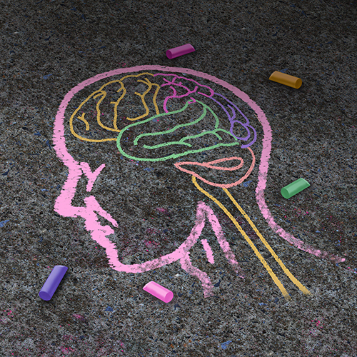Colorful chalk drawing of a facial profile on asphalt
