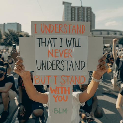 Individual holding a sign that read I understand that I will never understand, but I stand with you. -BLM