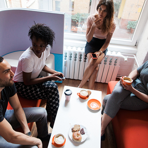 A group of 4 sitting and talking in a small space