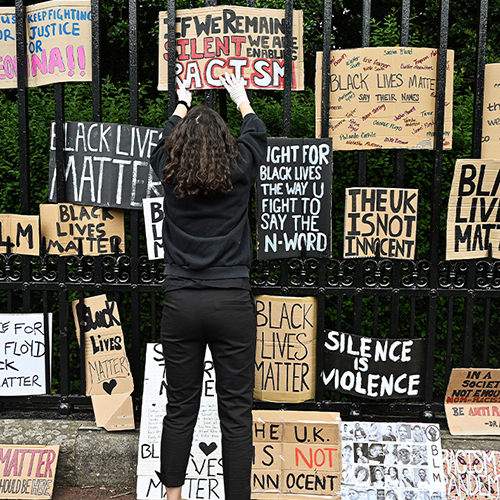A woman displaying a BLM protest sign on a fence with other BLM protest signs.