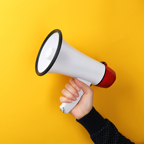 A hand holding a white megaphone against a yellow background