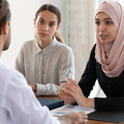 A white woman, and woman wearing a hijab, and a white male having a discussion