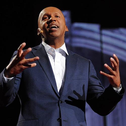 A bald black man in a blue suit giving a speech