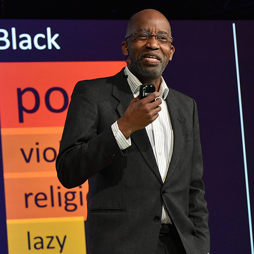 A black man with glasses and wearing a black suit giving a speech