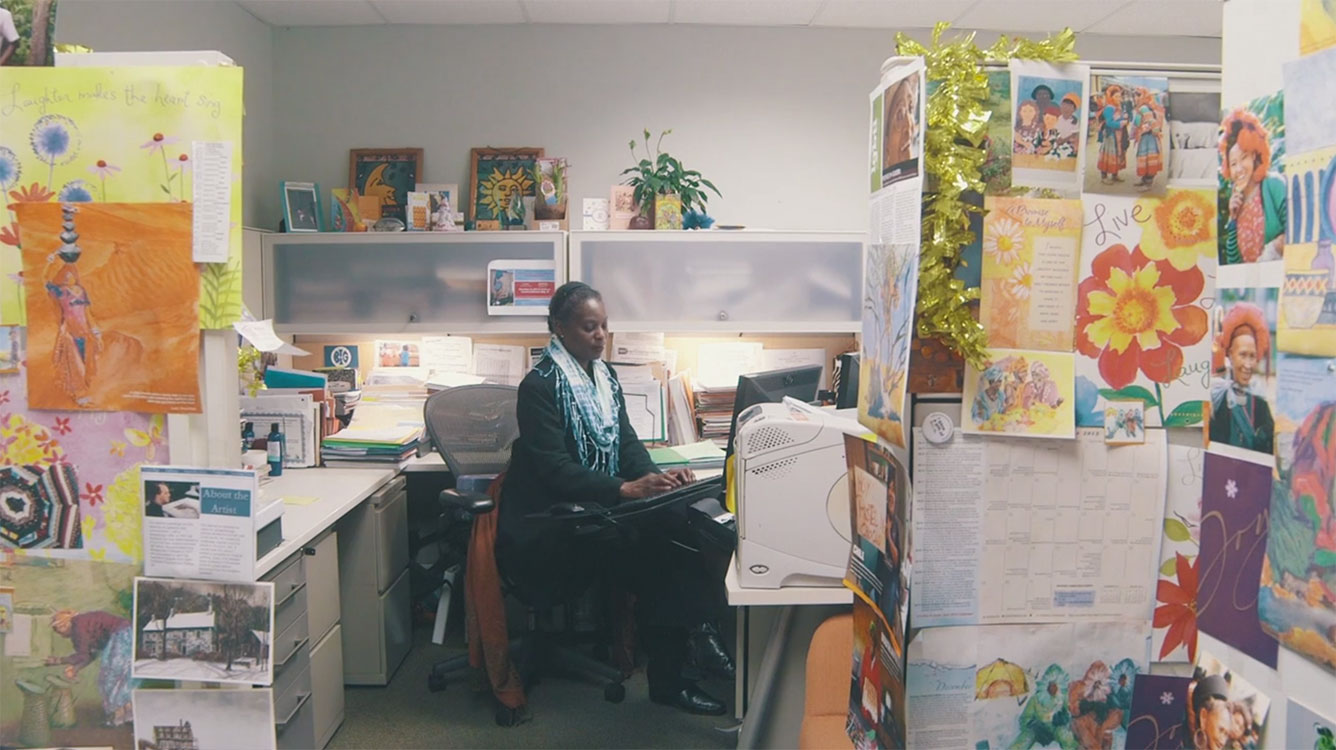 Alfreda Layne working in her colorful and highly decorated cubicle.