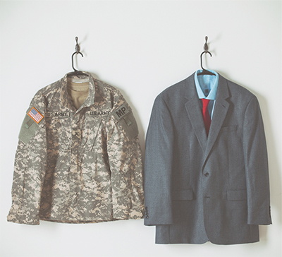 A US Army Uniform and a suit hung on the wall.