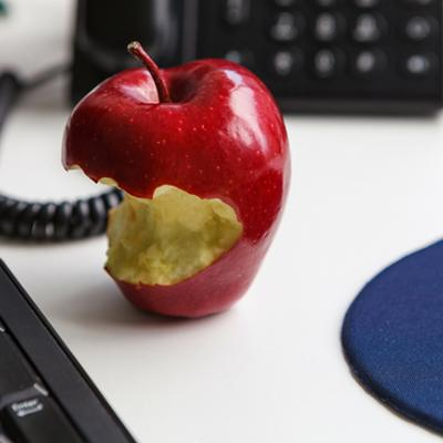 A half eaten apple sitting on a desk next to a keyboard and a telephone.