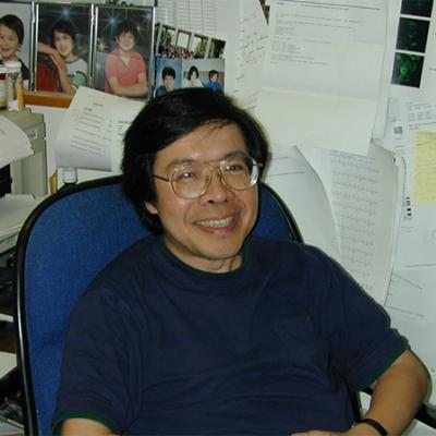 Dr. Kuan-Teh Jeang sitting at his desk.