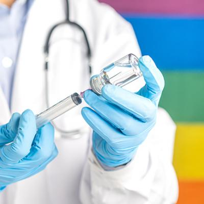 Person in lab coat and gloves uses syringe in front of Pride flag background