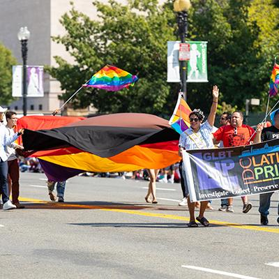 Members of the Latinx community marching and waving flags at 2019 Washington DC Pride parade