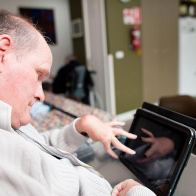 Man with a disability using a tablet device while seated.