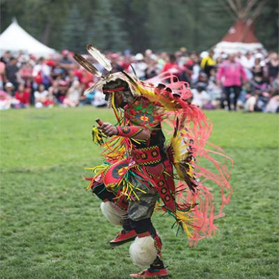 Native American man wearing full regalia dancing at a powwow.