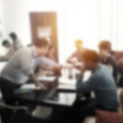 A deliberately out of focus image of people sitting at a table having a meeting.