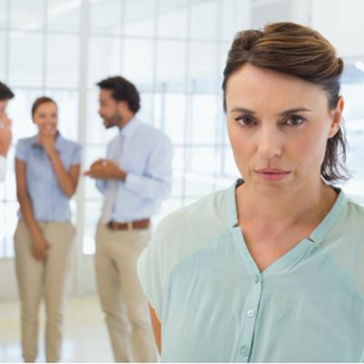 A sad businesswoman standing in front of a group of colleagues who are gossiping about her at the office.