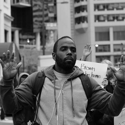 A young black man protesting with his hands up.