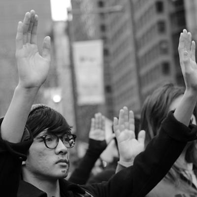 A young asian man protesting with his hands up.