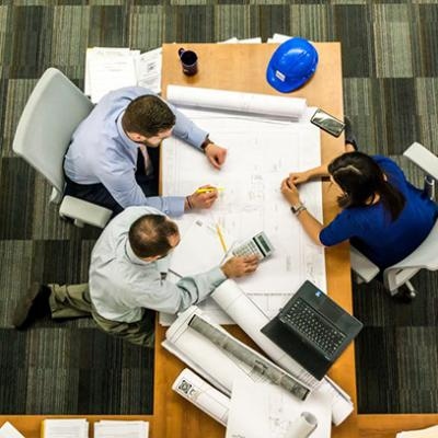 Overhead shot of 3 people sitting at a table collaborating on a project.